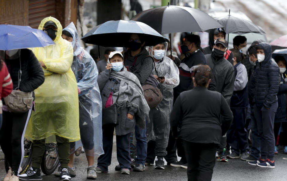 People line up outside a polling station during general elections in La Paz, Bolivia, Sunday, Oct. 18, 2020. (AP Photo/Martin Mejia)