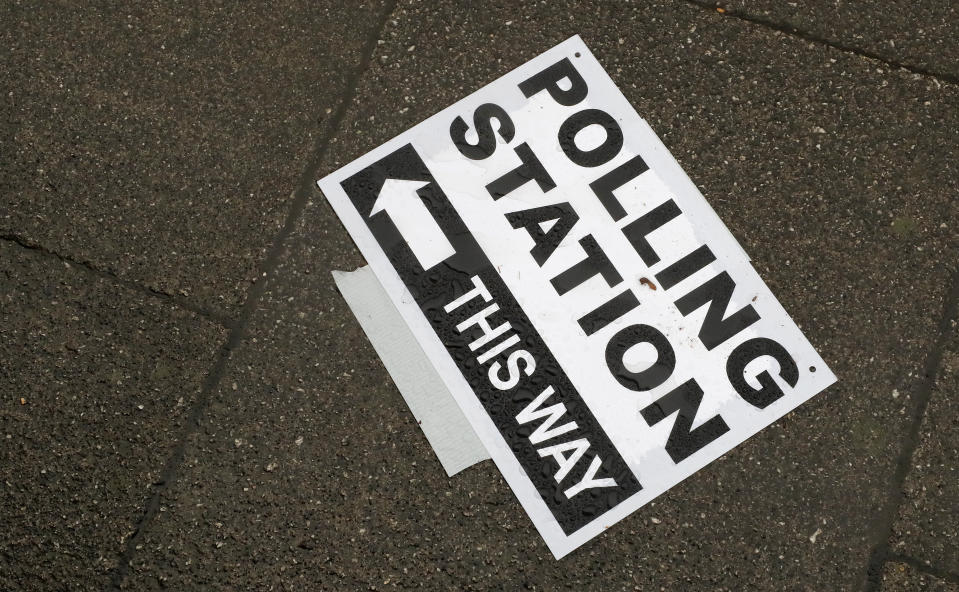 A polling station signpost lies on the pavement, in Twickenham, England, Thursday, Dec. 12, 2019. British voters are deciding who they want to resolve the Brexit conundrum in an election seen as one of the most important since the end of World War II.  (AP Photo/Frank Augstein)