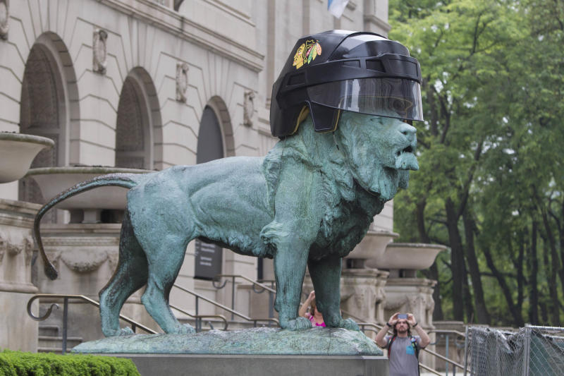 A passerby takes a photograph of an oversized Chicago Blackhawks hockey helmet sitting on one of the lion sculptures outside the entrance to the Art Institute of Chicago in celebration of the team's upcoming appearance in the Stanley Cup finals Wednesday, June 12, 2013, in Chicago. The Blackhawks host the Boston Bruins in Game 1 on Wednesday. (AP Photo/Scott Eisen)