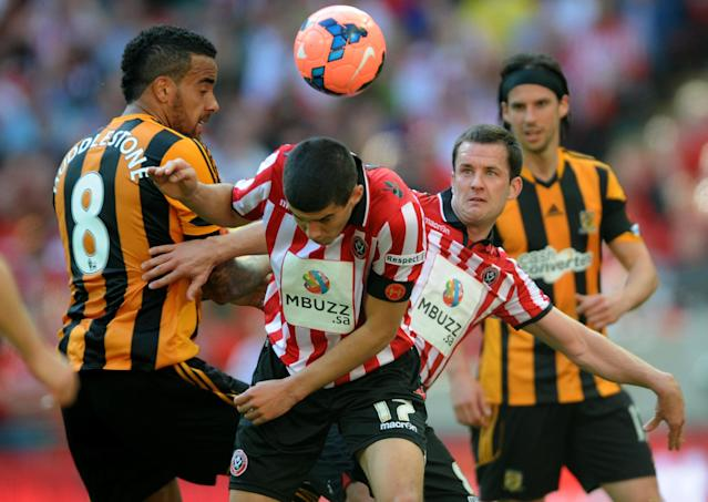 Sheffield United's Michael Doyle, second left, and teammate Conor Coad, second right,, contest the same ball with Hull City's Tom Huddlestone, left. during their English FA Cup semifinal soccer match between Hull City and Sheffield United at Wembley Stadium, London, England, Sunday, April 13, 2014. (AP Photo/Rui Vieira)