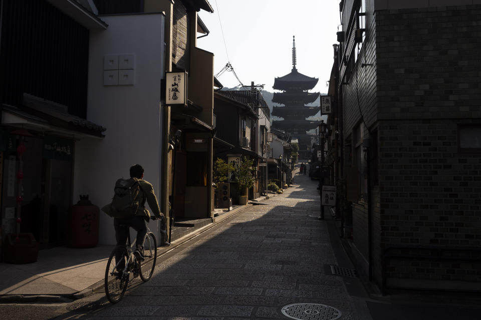 A man rides his bike toward Yasaka Pagoda in the Higashiyama district of Kyoto, Japan, March 19, 2020. Kyoto's city government has an emergency fund for small to medium-size businesses who suffered sharp sales decline since the coronavirus outbreak. (AP Photo/Jae C. Hong)