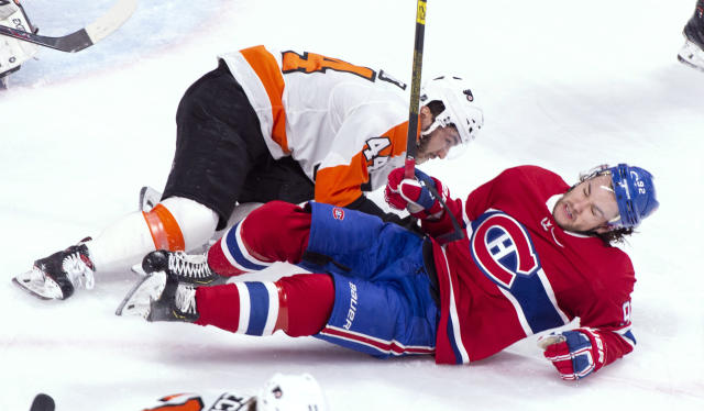 Montreal Canadiens' Jonathan Drouin (92) and Philadelphia Flyers' Phil Varone fall during the first period of an NHL hockey game Thursday, Feb. 21, 2019, in Montreal. (Paul Chiasson/The Canadian Press via AP)