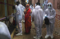 A woman covers her face as she walks past health workers arriving to administer a free medical checkup in a slum in Mumbai, India, Sunday, June 28, 2020. India is the fourth hardest-hit country by the COVID-19 pandemic in the world after the U.S., Russia and Brazil. (AP Photo/Rafiq Maqbool)