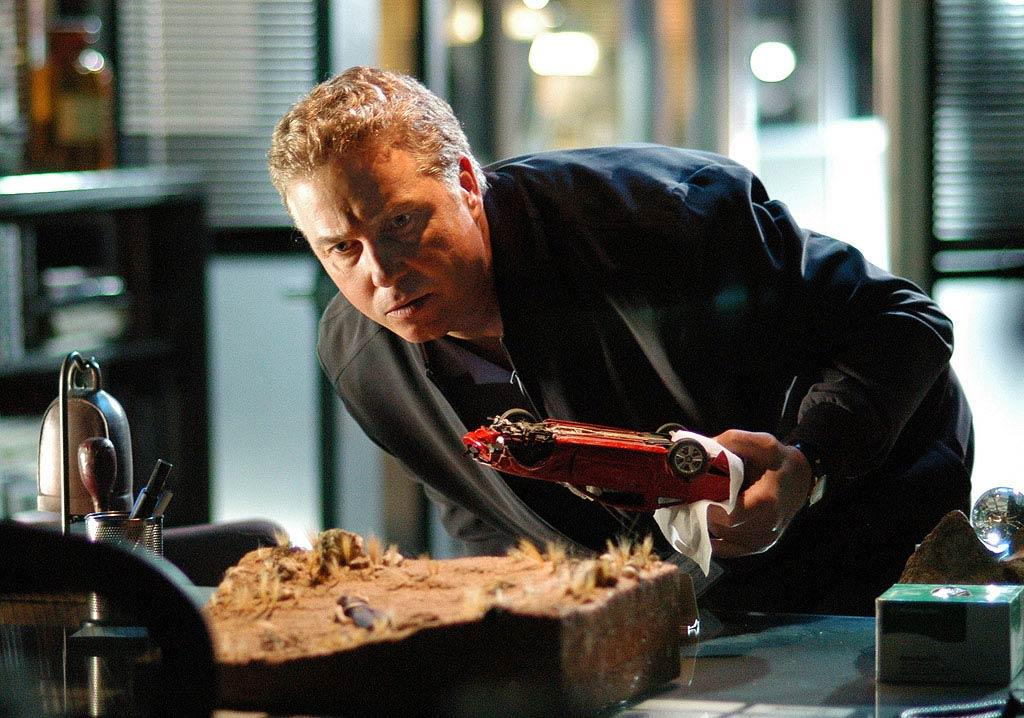 """The CSI team is hot on the trail of the miniature killer, who taunts Grissom by sending a disturbing new miniature representing Sara Sidle trapped under a car in the Vegas desert. (""""Living Doll"""" 5/17/2007, Season 7 Finale)"""