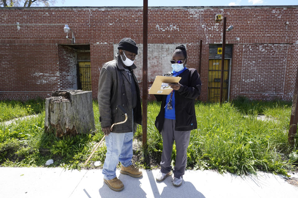Kenneth West, left, talks with registered nurse Precious McCormick about receiving a Moderna COVID-19 vaccine, in Detroit, Wednesday, May 12, 2021. In three weeks, more than 40 people have received vaccinations through the program to reach people who normally have little to no access to churches, community centers or other places where vaccines are being given. Mobile care teams consisting of two nurses and a peer support specialist accompany The Salvation Army's Bed & Bread trucks as they cruise Detroit, which lags far behind the state and nearby communities in percentage of people vaccinated. (AP Photo/Paul Sancya)