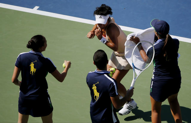 Ball persons attempt to swat away a bee from Kimiko Date-Krumm, of Japan, during the opening round of the 2014 U.S. Open tennis tournament against Venus Williams, of the United States, Monday, Aug. 25, 2014, in New York. (AP Photo/Elise Amendola)