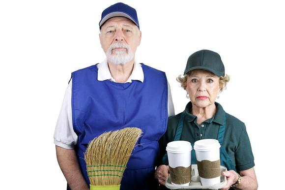 Two seniors with unhappy expressions wearing work clothes.