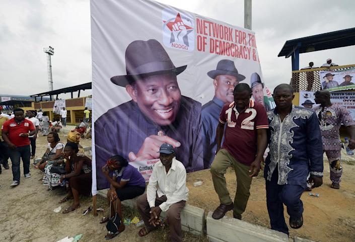 Supporters walk past a poster of the Nigerian President and presidential candidate of the ruling People's Democratic Party Goodluck Jonathan during an election rally in Port Harcourt on January 28, 2015 (AFP Photo/Pius Utomi Ekpei)