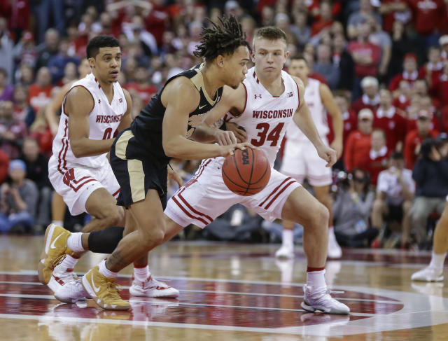 Purdue's Carsen Edwards (3) drives against Wisconsin's D'Mitrik Trice, left, and Brad Davison (34) during overtime of an NCAA college basketball game Friday, Jan. 11, 2019, in Madison, Wis. Edwards had a game-high 36 points in Purdue's 84-80 win. (AP Photo/Andy Manis)