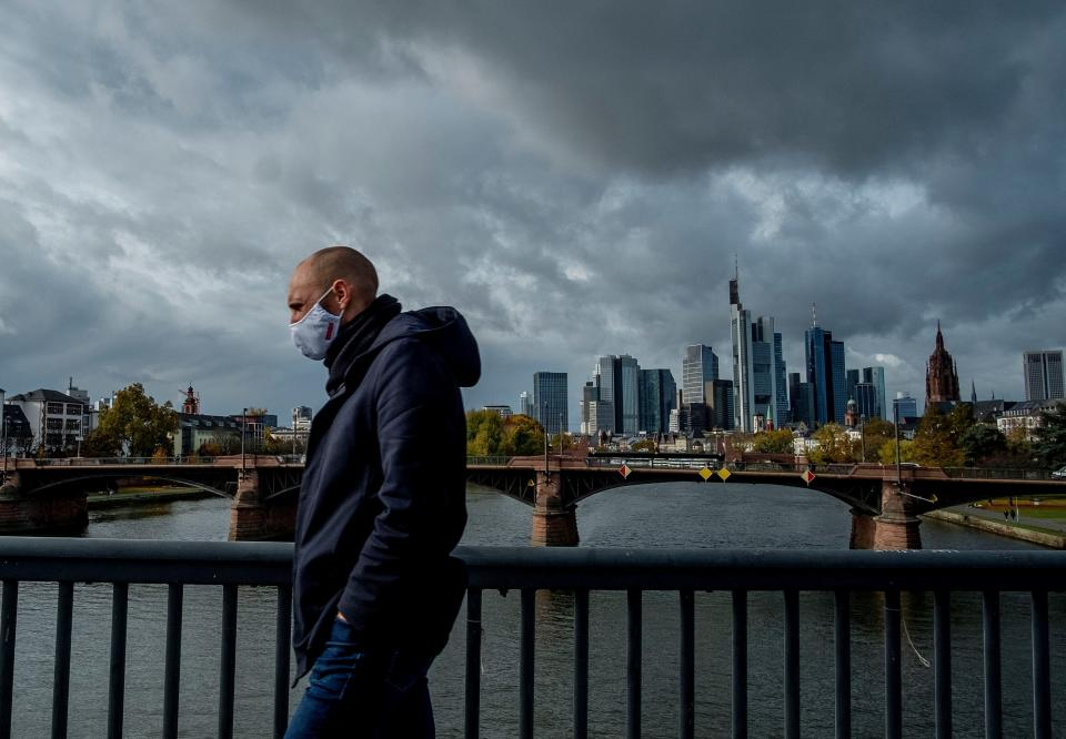 A man wearing a face mask walks over a bridge with the buildings of the banking district in background in Frankfurt, Germany, Thursday, Oct. 29, 2020. (AP Photo/Michael Probst)