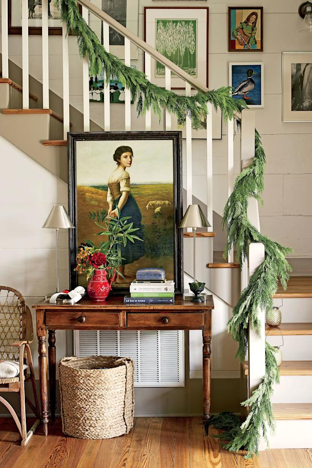 <p>Less is more in this eclectic farmhouse. Simple garland draped around the handrail sets the tone for a cozy Christmas. </p>