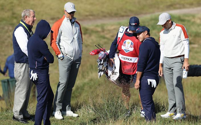 A rules lawyer inspects the lie of a ball for Daniel Berger and Brooks Koepka on the 15th hole - Getty Images