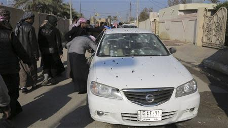 Residents inspect a bullet-riddled car outside the house of prominent Sunni Muslim lawmaker Ahmed al-Alwani in the centre of Ramadi, December 28, 2013. REUTERS/Ali al-Mashhadani