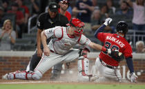 Atlanta Braves' Nick Markakis (22) beats the tag from Philadelphia Phillies catcher J.T. Realmuto (10) to score on an Ozie Albies base hit during the eighth inning of a baseball game Friday, June 14, 2019, in Atlanta. (AP Photo/John Bazemore)