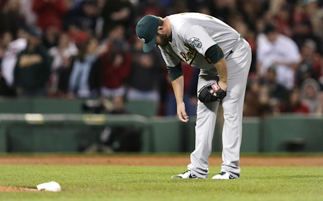 Oakland Athletics relief pitcher Ryan Cook pauses behind the pitcher's mound after giving up a grand slam to Boston Red Sox's Dustin Pedroia during the sixth inning of a baseball game at Fenway Park in Boston, Friday, May 2, 2014. (AP Photo/Charles Krupa)