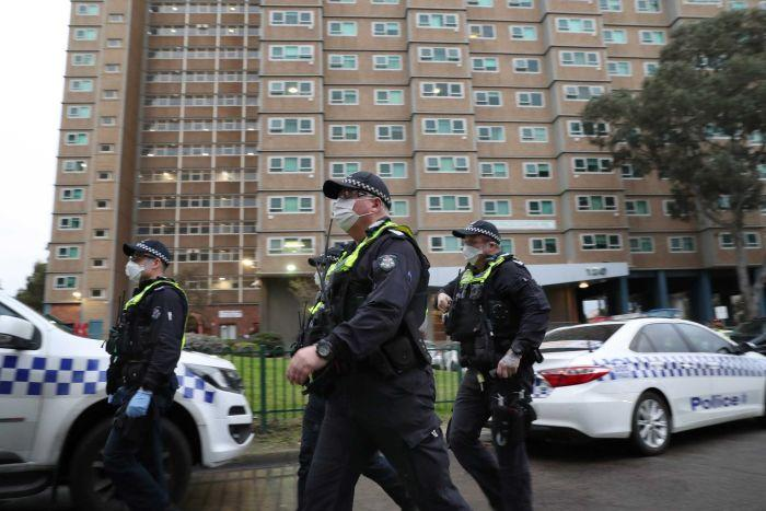 Police wearing face masks walk in front of a public housing block.