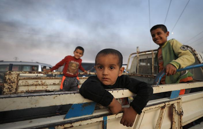 Boys stand at a back of a truck as they flee Ras al Ain town, Syria Oct. 9, 2019. (Photo: Rodi Said/Reuters)