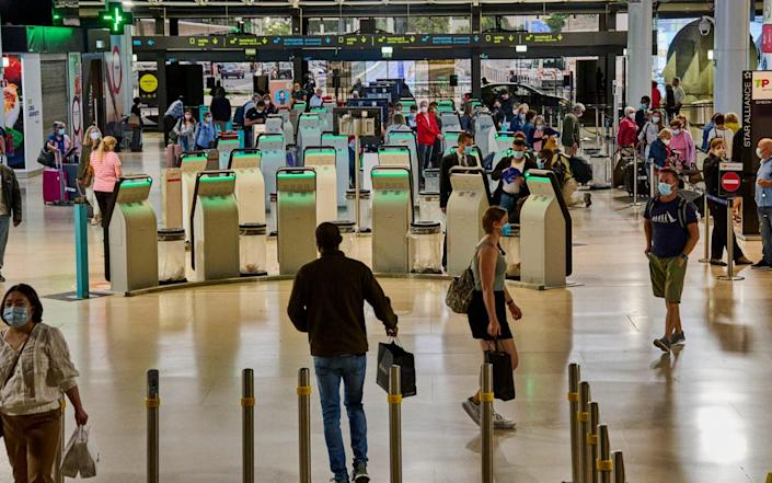 In Lisbon, Portugal, mask-clad departing travellers use the self check-in machines and queue - Horacio Villalobos/Corbis via Getty Images