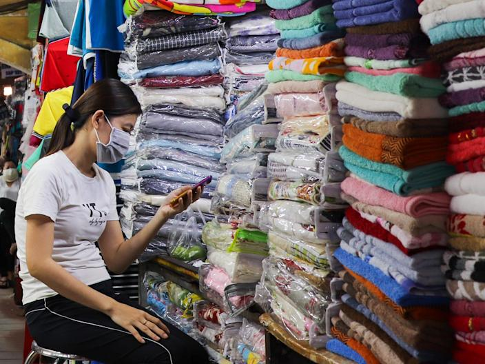 A shopkeeper at Ben Thanh Market in Ho Chi Minh City, Vietnam, checks her phone.