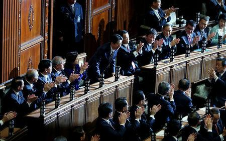 Japan's Prime Minister Shinzo Abe (C) bows as he is re-elected as prime minister while his party lawmakers clap their hands at the Lower House of Parliament in Tokyo, Japan, November 1, 2017. REUTERS/Toru Hanai