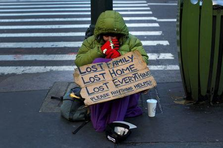 A homeless woman sits bundled against the cold as she begs for handouts on East 42nd Street in the Manhattan borough of New York City, January 4, 2016. REUTERS/Mike Segar