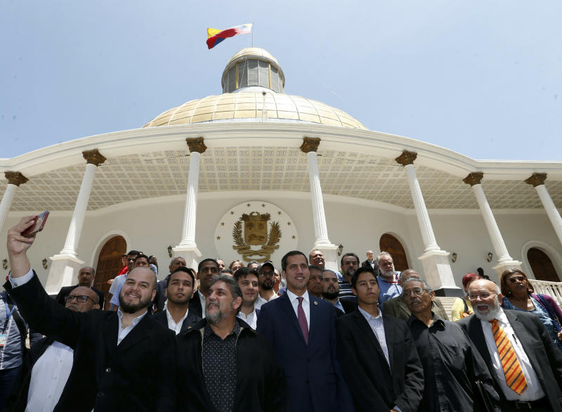 Venezuelan opposition leader Juan Guaido, center right, who has declared himself interim president, poses for a photo with members of a coalition of opposition parties, and other civic groups after their meeting in Caracas, Venezuela, Monday, March 18, 2019. After Guaido declared himself interim president in late Feb., Venezuelan President Nicolas Maduro has remained in power despite heavy pressure from the United States and other countries arrayed against him, managing to retain the loyalty of most of his military leaders. (AP Photo/Natacha Pisarenko)