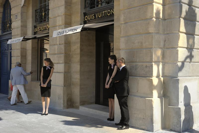 Hostesses stand in front of the entrance of LVMH's Louis Vuitton's jewellery store on Place Vendome during its opening day in Paris July 2, 2012. REUTERS/Philippe Wojazer