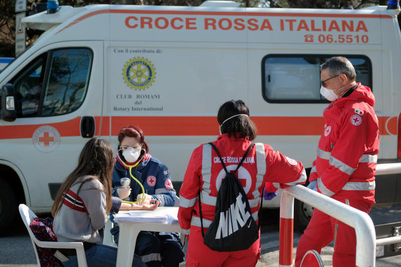 A woman donates blood at a Red Cross mobile unit in Rome, Saturday April 4, 2020. The government is demanding Italians stay home and not take the leveling off of new coronavirus infections as a sign the emergency is over, following evidence that more and more Italians are relaxing restrictions the west's first and most extreme nationwide lockdown and production shutdown. (Mauro Scrobogna/LaPresse via AP)