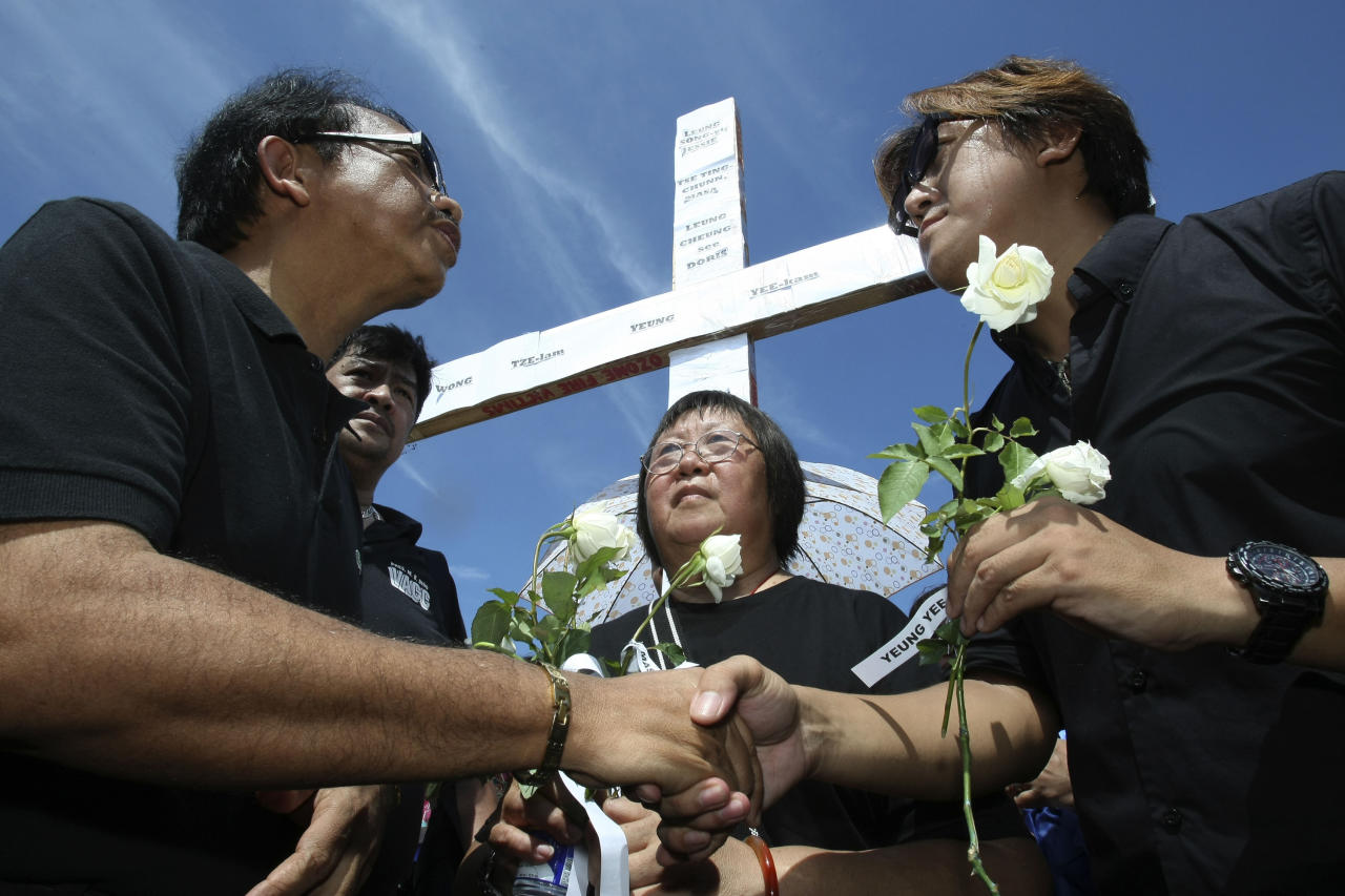 Dante Jimenez, left, head of a private watchdog Volunteers Against Crime and Corruption, gives white roses as he conveys his sympathies to Tse Chi Kin, right, brother of the late Masa Tse, a Hong Kong tour guide who was the first to be killed by a dismissed policeman who took Hong Kong tourists hostage, during a ceremony to mark the first anniversary of the botched bus hostage drama Tuesday Aug. 23, 2011 in Manila, Philippines. Eight Hong Kong tourists were killed in the botched hostage rescue when the dismissed policeman took them hostage exactly a year ago Tuesday. In the center is Lee Mei Chun, mother of the late Masa Tse. (AP Photo/Bullit Marquez)