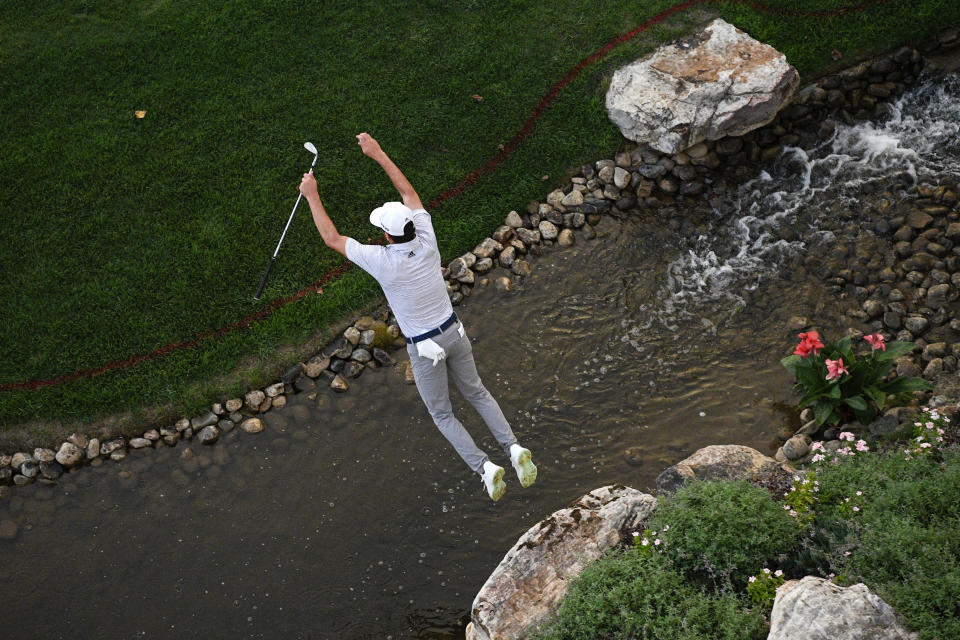 Joaquin Niemann, of Chile, leaps over a creek after looking for his ball in the rough near the 18th green during the second round of the BMW Championship golf tournament, Friday, Aug. 27, 2021, at Caves Valley Golf Club in Owings Mills, Md. (AP Photo/Nick Wass)