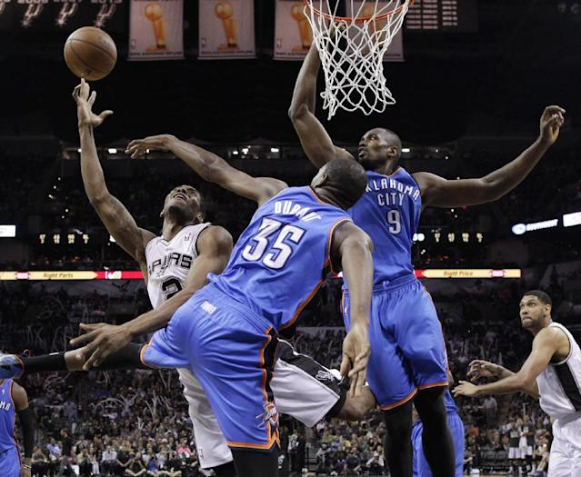 San Antonio Spurs' Kawhi Leonard (2) shoots over Oklahoma City Thunder's Kevin Durant (35) and Serge Ibaka (9) during the second half of Game 5 of the Western Conference finals NBA basketball playoff series, Thursday, May 29, 2014, in San Antonio. San Antonio won 117-89. (AP Photo/)