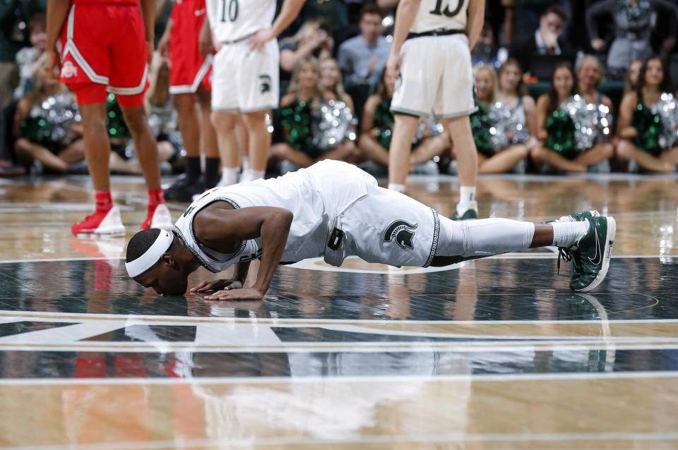 Michigan State's Cassius Winston kisses the court as he comes out late of an NCAA college basketball game against Ohio State in the second half Sunday, March 8, 2020, in East Lansing, Mich. (AP Photo/Al Goldis)