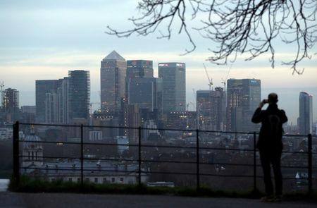 FILE PHOTO: A man takes a photograph of the Canary Wharf financial district from Greenwich Park in London