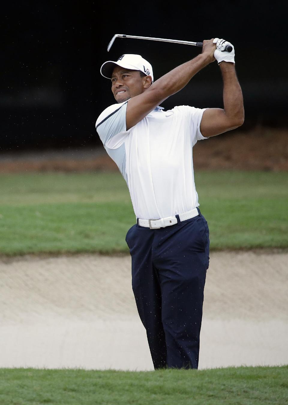 Tiger Woods hits out of the bunker on the fourth hole during the third round of play in the Tour Championship golf tournament at East Lake Golf Club, in Atlanta, Saturday, Sept. 21, 2013. (AP Photo/David Goldman)
