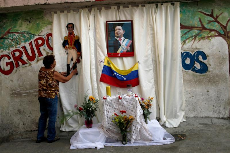 A woman places an image of Venezuela's independence hero Simon Bolivar on an altar set up on a sidewalk in honor of late President Hugo Chavez, whose picture hangs on the curtain, along a street where a procession will pass tomorrow to transfer Chavez's body to a military museum in Caracas, Venezuela, Thursday, March 14, 2013. Venezuela's acting president said Wednesday that it is highly unlikely Chavez will be embalmed for permanent viewing because the decision to do so was made too late and the socialist leader's body was not properly prepared on time. Chavez's body has been lying in state at the military academy since March 6. (AP Photo/Rodrigo Abd)