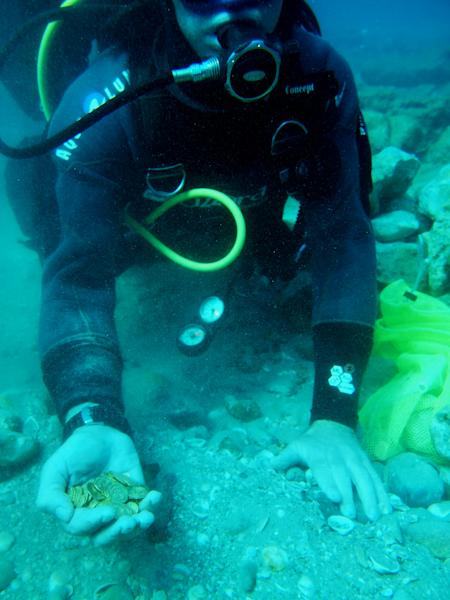 A handout picture released by Israel's Antiquities Authority shows a scuba diver holding in his hand some of the gold coins found on the seabed in the ancient harbour in Caesarea (AFP Photo/Kobi Sharvit)