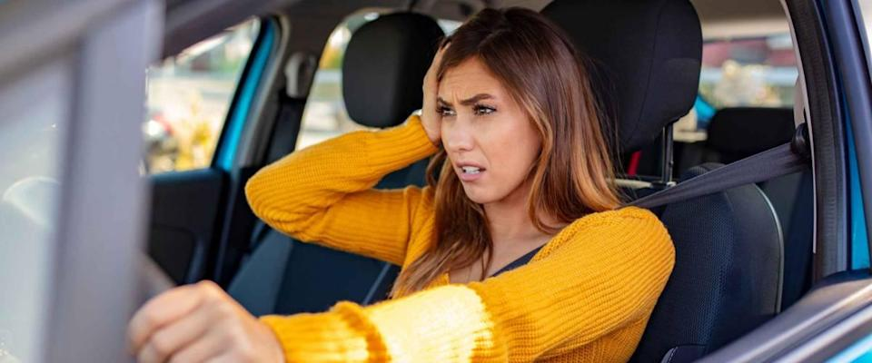 Nervous female driver sits at wheel, worried about paying too much for car insurance