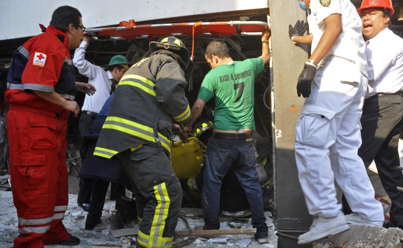 Firefighters belonging to the Tacubaya sector and emergency responders pull out a survivor after an explosion at an adjacent building to the executive tower of Mexico's state-owned oil company PEMEX, in Mexico City, Thursday Jan. 31, 2013. A large explosion occurred in the lower floors of the building and dozens have been reported injured so far. (AP Photo/Guillermo Gutierrez)