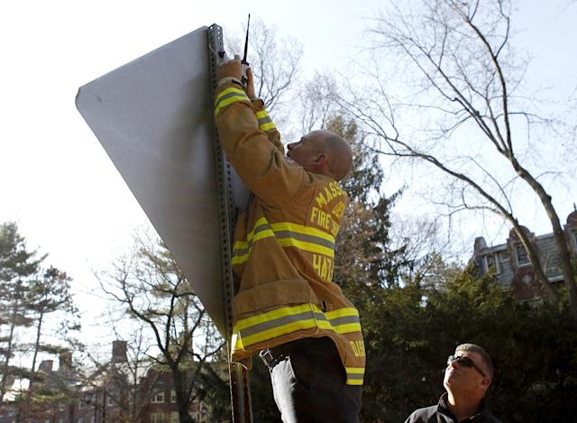 A member of the Massachusetts Department of Fire Services Haz-Mat crew affixes a device to the back of a street sign in front of Wellesley College before the start of the 118th Boston Marathon Monday, April 21, 2014 in Wellesley, Mass.. (AP Photo/Mary Schwalm)
