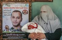 Iman al-Qudra, wife of Palestinian prisoner Mohammad, seen in the poster, holds their newborn boy, conceived with his smuggled sperm