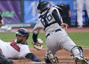 Cleveland Indians' Eddie Rosario, left, slides safely into home plate as New York Yankees' Kyle Higashioka is late on the tag in the first inning of a baseball game, Thursday, April 22, 2021, in Cleveland. (AP Photo/Tony Dejak)