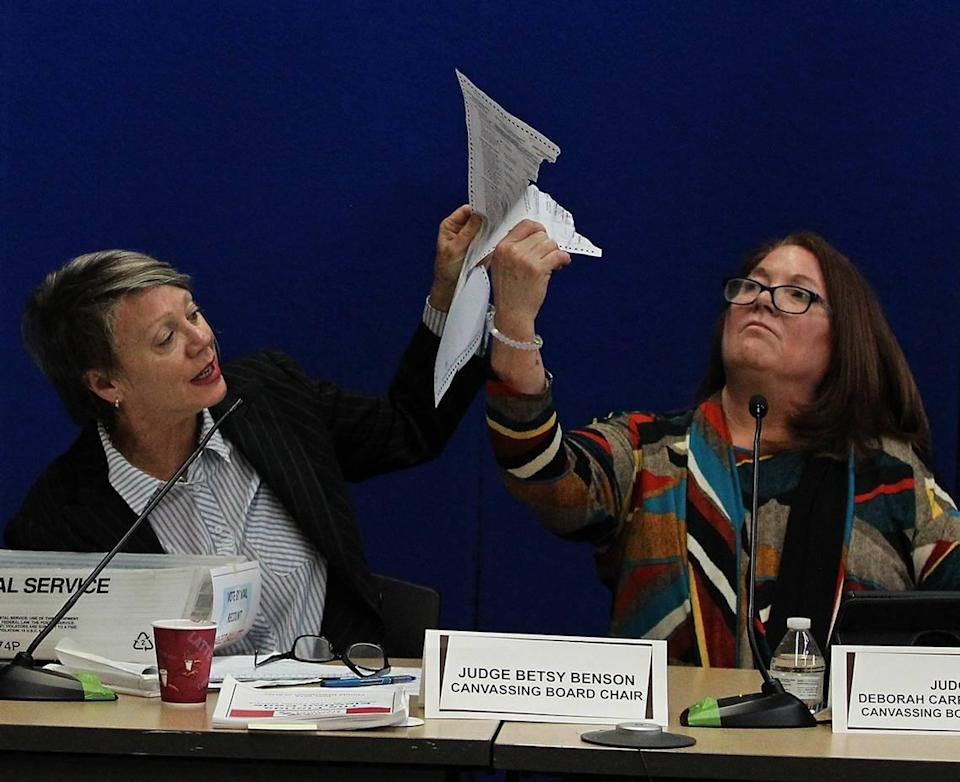 Judge Betsy Benson, canvassing board chair, left, and Judge Deborah Carpenter-Toye, canvassing board member, examine a damaged ballot as the election recount continues in Broward County on Wednesday, Nov. 14, 2018.