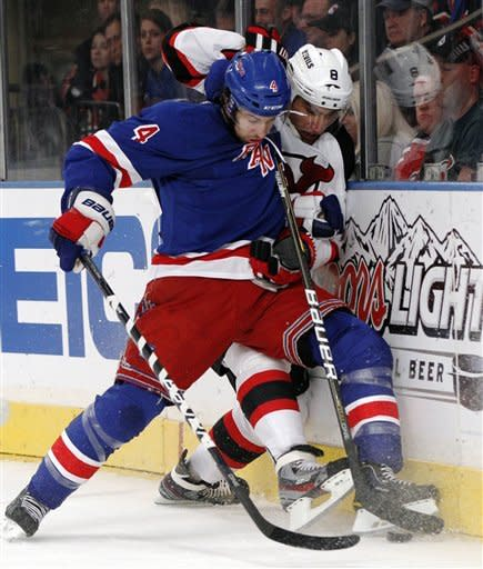 New York Rangers defenseman Michael Del Zotto (4) checks New Jersey Devils right wing Dainius Zubrus (8) against the boards during the first period of Game 1 of their NHL hockey Stanley Cup Eastern Conference final playoff series at New York's Madison Square Garden, Monday, May 14, 2012. (AP Photo/Kathy Willens)
