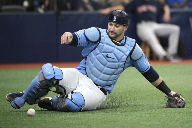 FILE - In this Sept. 22, 2019, file photo, Tampa Bay Rays catcher Mike Zunino slides to pick up a wild pitch from relief pitcher Andrew Kittredge during the fourth inning of a baseball game in St. Petersburg, Fla. Making it safe for America's professional sports teams to start playing games is one thing. Making sure athletes are in game shape is another. Experts say nothing should be rushed. Athletes in the NBA, NHL and Major League Baseball all indicate that a few weeks of training is necessary before any games. (AP Photo/Phelan M. Ebenhack, File)
