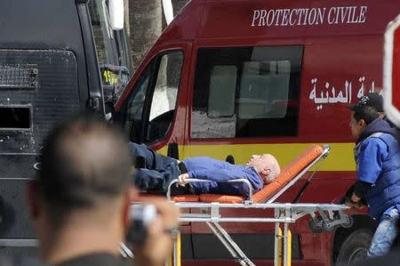 A tourist injured after an attack by gunmen on Tunisia's national museum is wheeled on a stretcher in Tunis March 18, 2015. REUTERS/Stringer