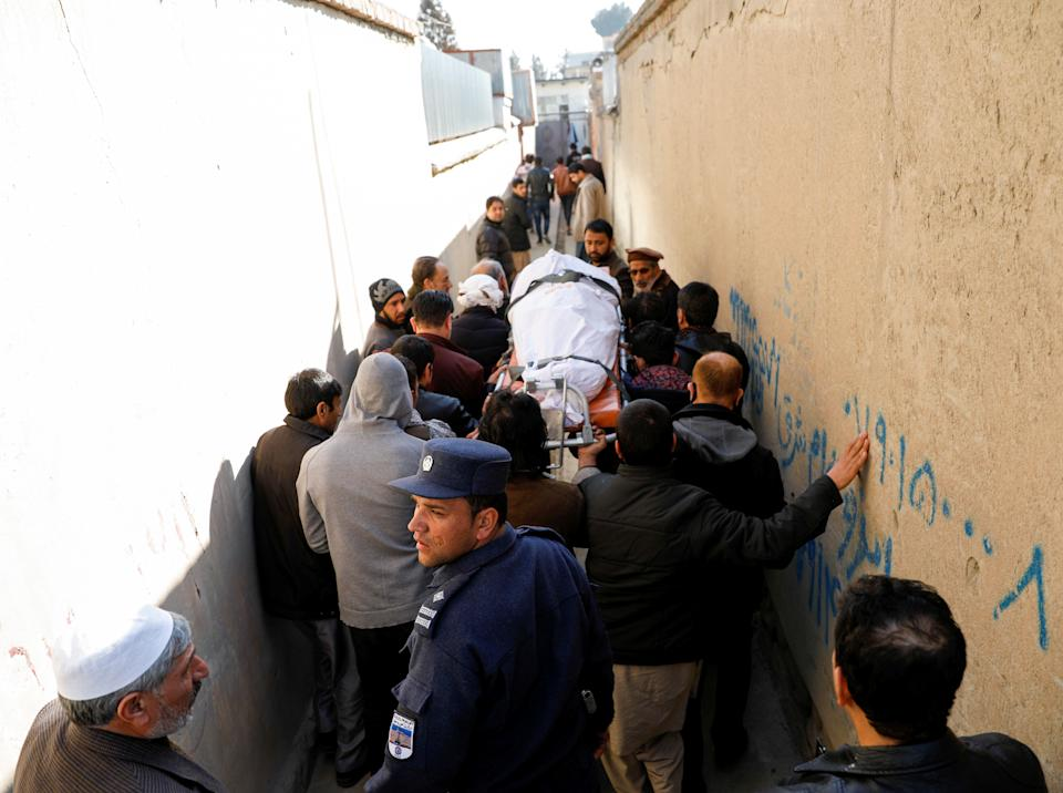 <p>Relatives carry the body of one of female judges shot dead by unknown gunmen in Kabul</p> (REUTERS)