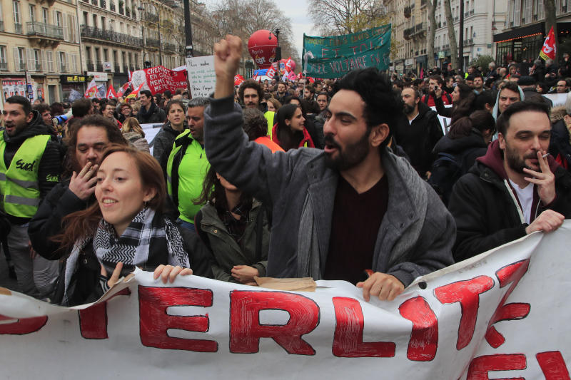Protesters march during a demonstration Thursday, Dec. 19, 2019 in Paris. Traffic improved slightly on French trains Thursday as nationwide strikes over the government's retirement reform entered a 15th day and small signs of progress emerged in negotiations with unions. (AP Photo/Michel Euler)