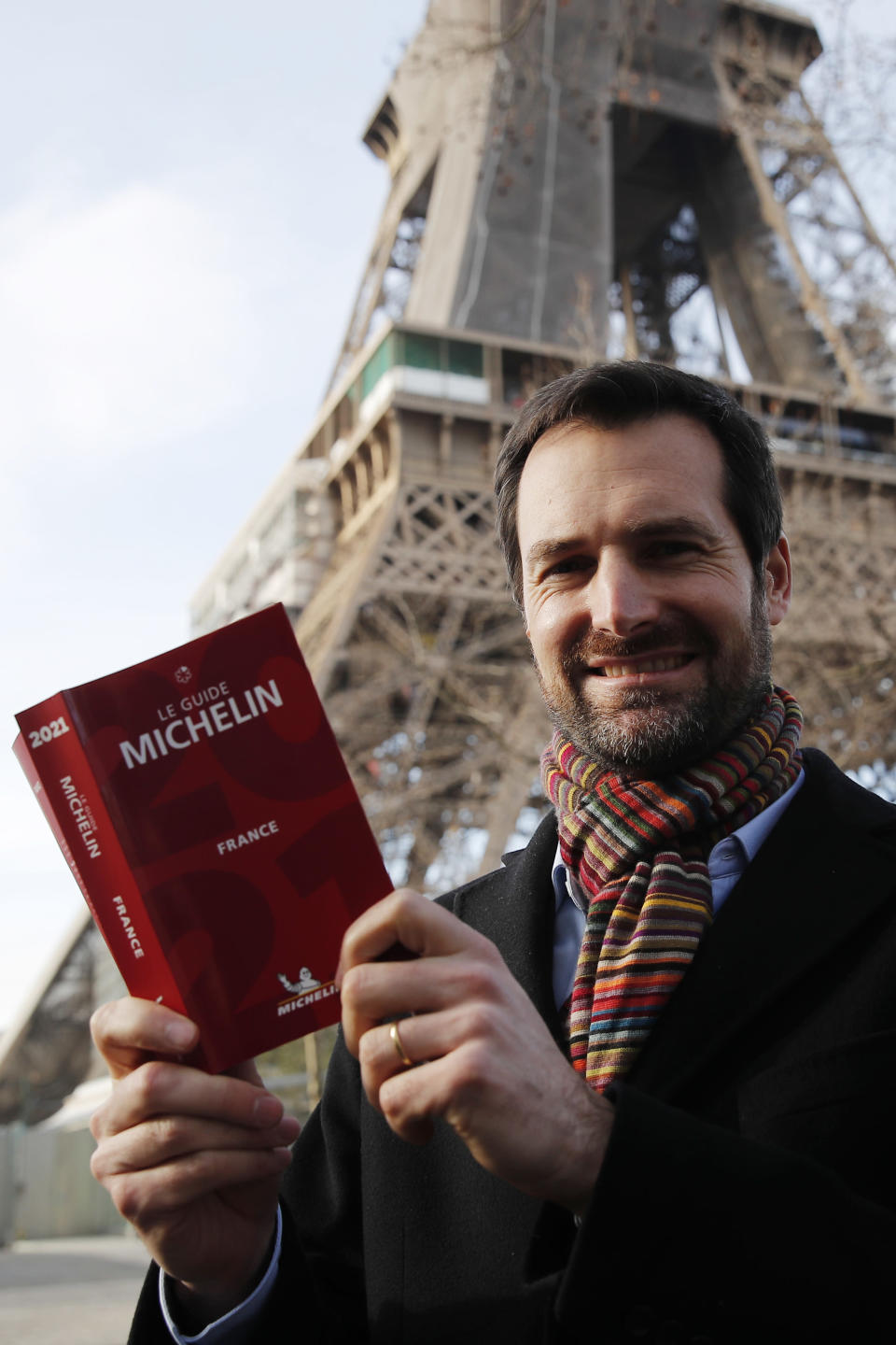 Gwendal Poullennec, head of Le Guide Michelin, poses with the 2021 edition outside the Eiffel Tower, Monday, Jan. 18, 2021 in Paris. Michelin will later announce the 2021 winners in a broadcast from the Eiffel Tower. (AP Photo/Francois Mori)