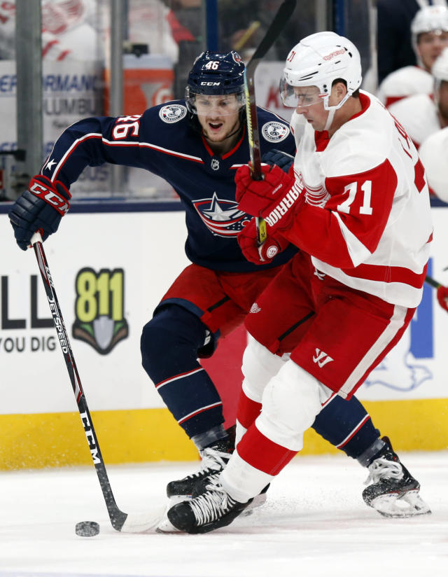 Detroit Red Wings forward Dylan Larkin, right, chases the puck in front of Columbus Blue Jackets defenseman Dean Kukan, of Switzerland, during the first period of an NHL hockey game in Columbus, Ohio, Thursday, Nov. 21, 2019. (AP Photo/Paul Vernon)