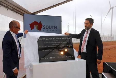 South Australian Premier, Jay Weatherill and Deputy CEO of Neoen, Romain Desrousseaux unveil a plaque during the official launch of the Hornsdale Power Reserve, featuring the world's largest lithium ion battery made by Tesla, near the South Australian town of Jamestown, in Australia, December 1, 2017. REUTERS/David Gray
